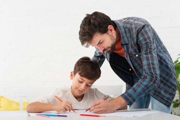 Father looking at his son doing homework