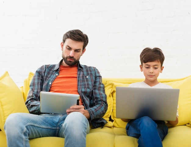 Father looking on tablet and son working on laptop