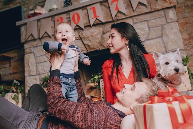 彼の妻が見えるとしながら、父は彼の息子と遊んで床に横たわっている暖炉の背景