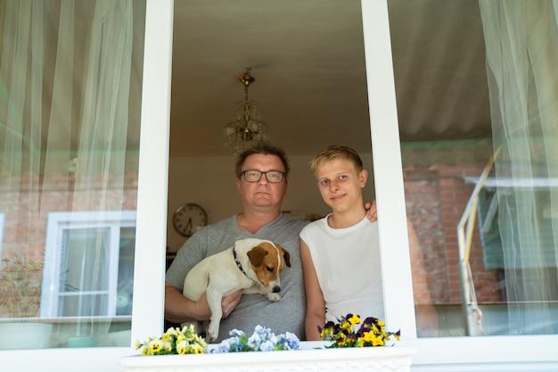 10代の息子を持つ父の男は、コロナウイルスのパンデミックから隔離されている間、彼の家の窓の外を見ています