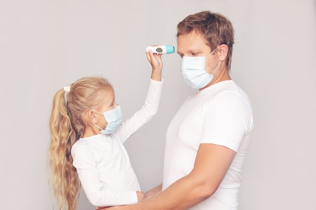 Father in a medical mask measures his daughter's temperature with an electronic thermometer on an isolated background