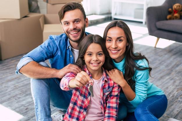 Отец, мать и дочь обнимаются, сидя на полу своей недавно купленной квартиры, держа ключи и широко улыбаясь.