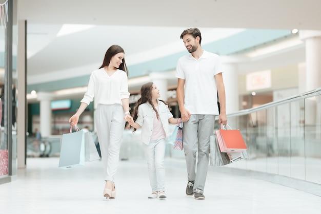 아버지, 어머니, 딸이 다른 가게로 걸어 가고있다