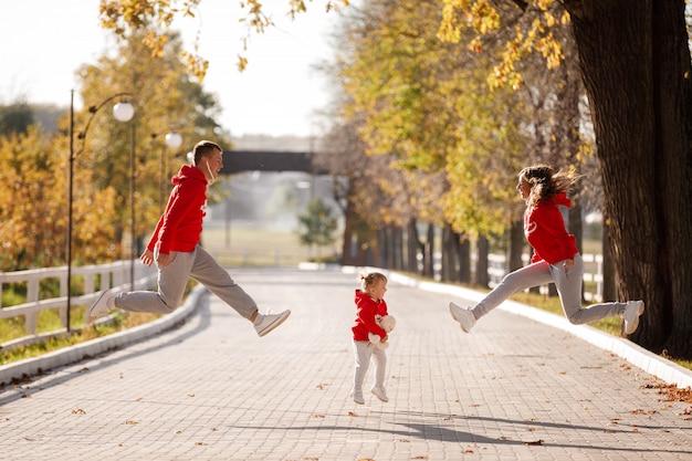 父、母、娘が秋の公園でジャンプします。