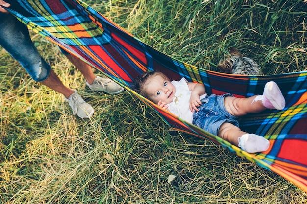 아버지, 어머니와 어린 딸이 야외에서 재미, 여름 공원에서 함께 연주