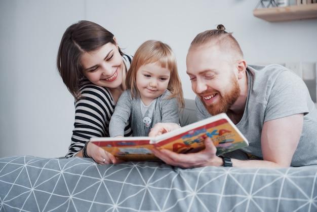 父、母、娘がリビングルームのソファーで子供向けの本を読んでいます。幸せな大家族がお祝いの日に面白い本を読んだ。親は子供を愛する