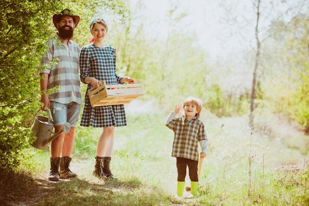 Отец-мать и маленькие мальчики веселятся на ферме весной, семья работает вместе на ферме