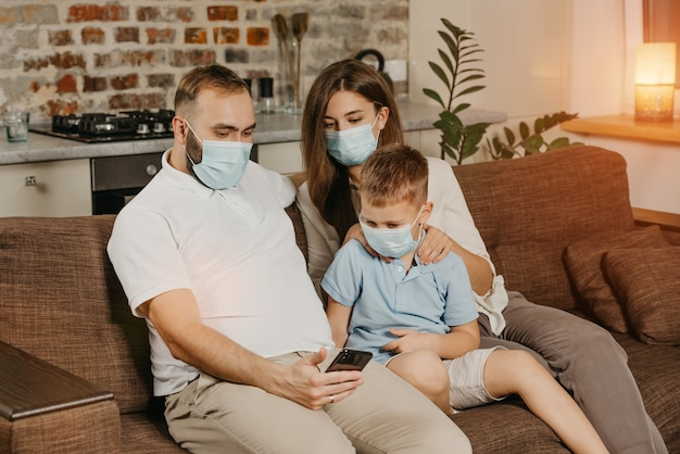 父、母、息子は、コロナウイルス(covid-19)の蔓延を防ぐために、医療用フェイスマスクのソファに座っています。