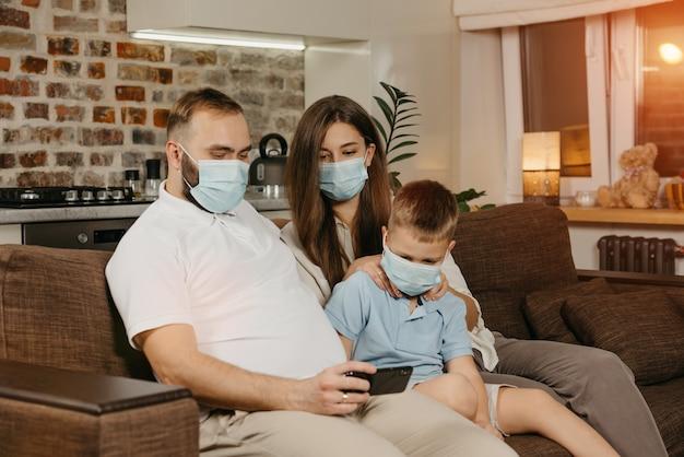 아버지, 어머니, 아들은 코로나 바이러스 (covid-19)의 확산을 피하기 위해 의료용 마스크를 쓰고 소파에 앉아 있습니다.