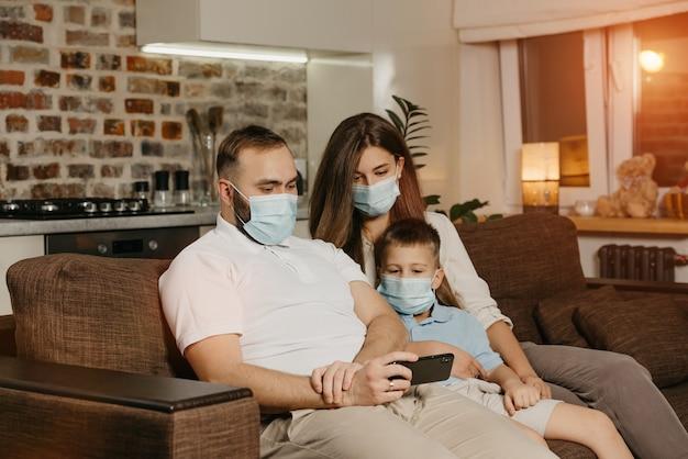 아버지, 어머니, 아들은 코로나 바이러스 (covid-19)의 확산을 피하기 위해 안면 마스크를 쓰고 소파에 앉아 있습니다.