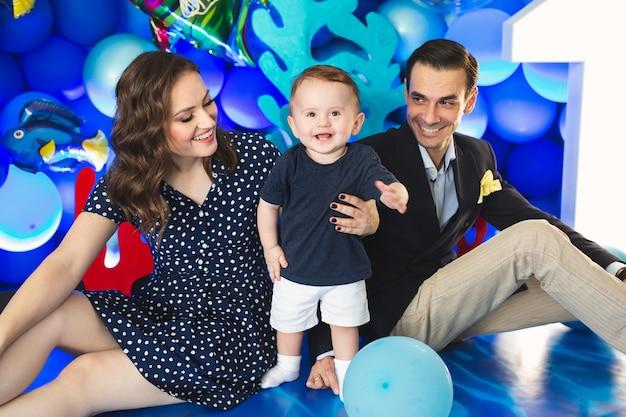 휴일에 마린 스타일에 파란색 장식의 배경에 아버지, 어머니와 아들.