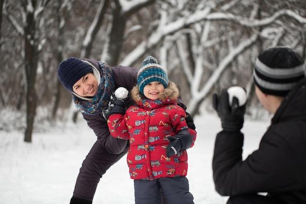 Отец, мать и сын играют в снежки зимой