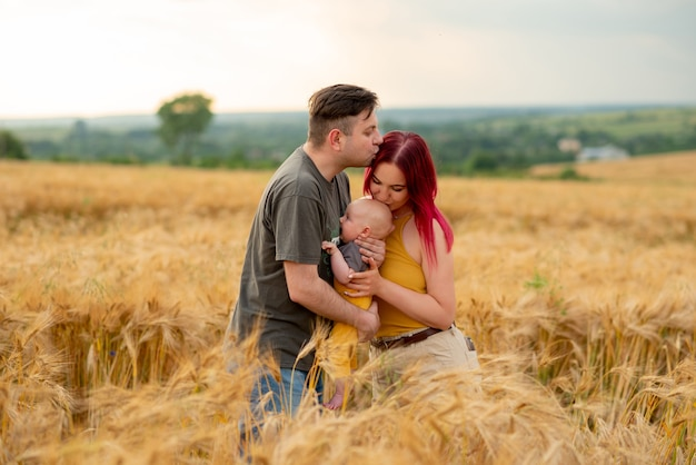 Отец, мать и их маленький сын веселятся вместе на пшеничном поле.