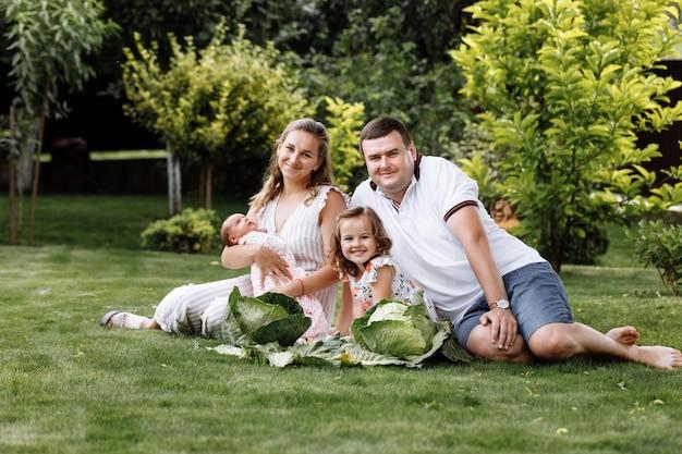 父、母と2人の子供、女の赤ちゃんとキャベツと草の上の小さな娘