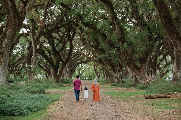 Отец, мать и двое детей гуляют в парке