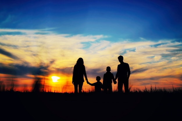 Father, mother, and children hold hands on a sunset background.