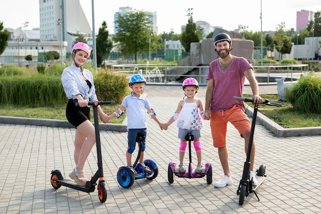 헬멧을 쓴 아버지, 어머니, 딸 및 아들은 전기 스쿠터를 타고 공원에 서 있습니다. 활동적인 라이프 스타일.