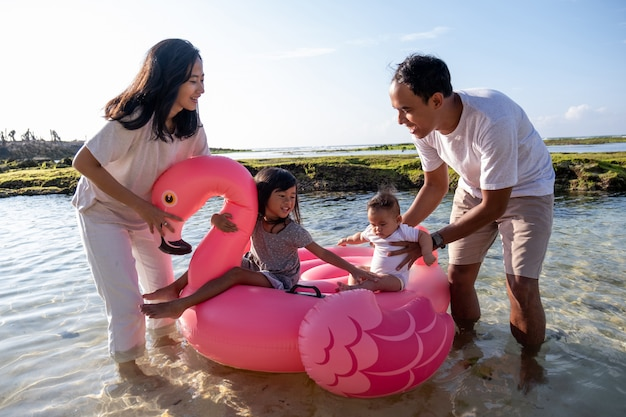 Father and mother holding the children riding a floating flamingo buoy in water
