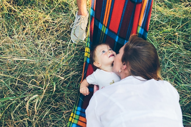 Father, mother and little daughter having fun outdoors, playing together in summer park