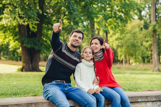 Father and mother sit between their daughter against trees or nature background