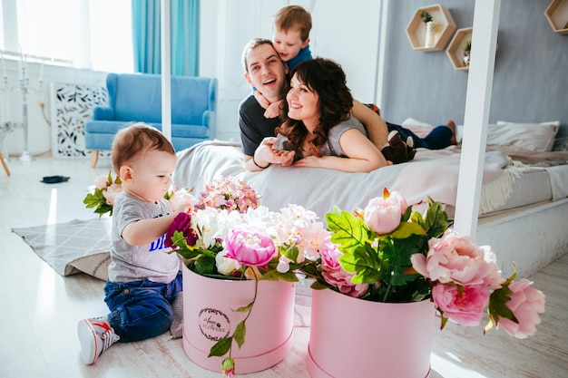 The father,mother and son lie on the bed and small son playing with flowers