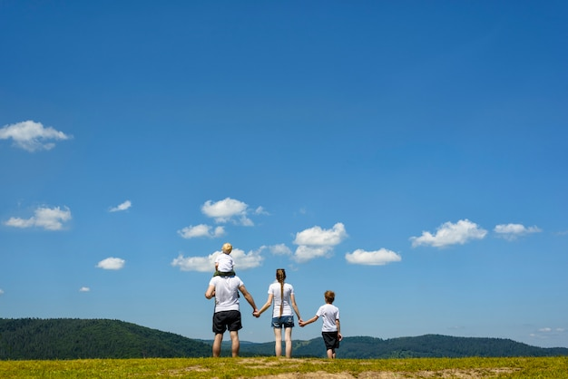 Father, mother and two little sons are standing on a green field. wooded hills, blue sky and clouds. family values