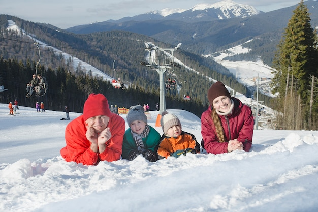Father, mother and two sons are lying and smiling against the background of a ski resort