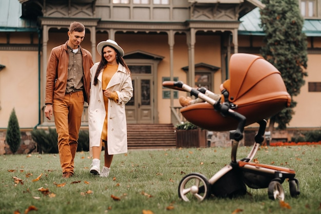 Father and mother on a walk with a child in a stroller in the autumn park on the background of the estate