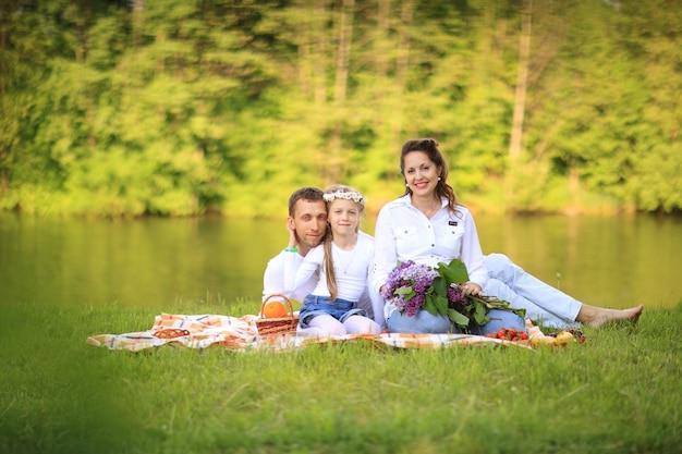 Отец, дочь и беременная мама на пикнике.
