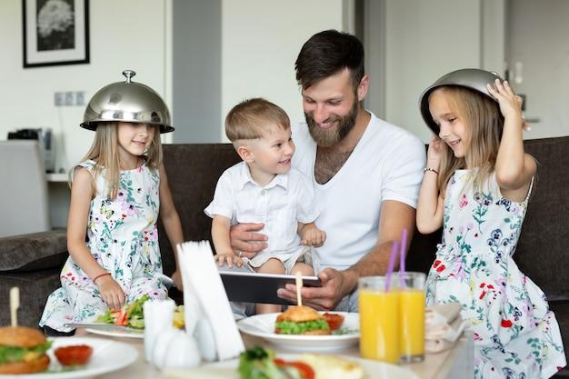 子供の父親はホテルの部屋で朝食をとり、遊んで楽しんでいます。