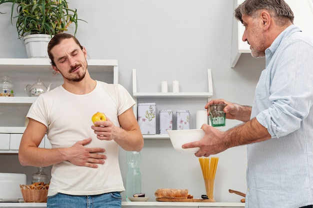 Father offering son a glass of water and a bowl
