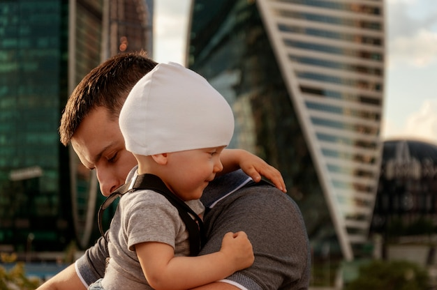 Father and one year old son against the sky and skyscrapers. travel with children, the development of emotional intelligence.
