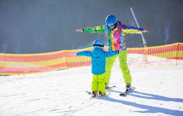 Отец или инструктор учит маленького мальчика кататься на лыжах