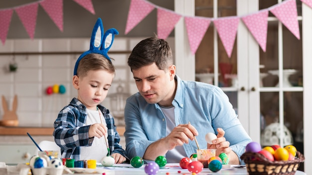 Father painting eggs with little boy for easter