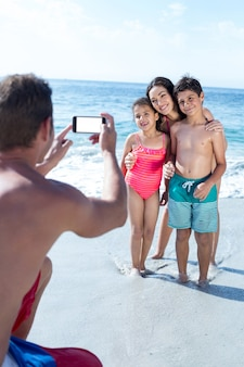 Father photographing children and wife at sea shore