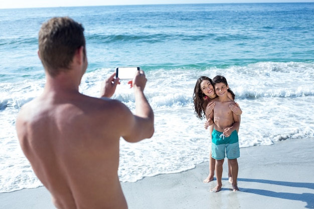 Father photographing happy wife and son