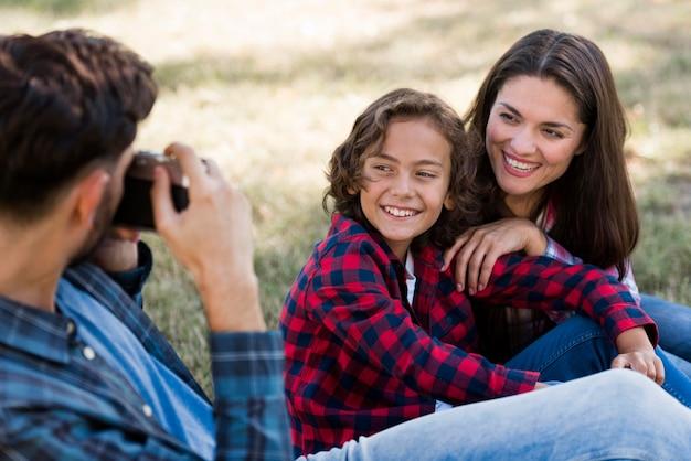 Отец фотографирует мать и сына на открытом воздухе в парке