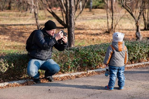 Отец фотографирует сына в парке