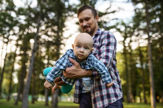 여름 공원에서 그의 작은 아기와 함께 아버지 놀이