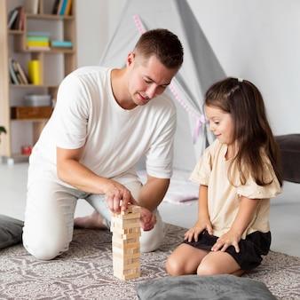 彼の娘と木製のゲームをしている父