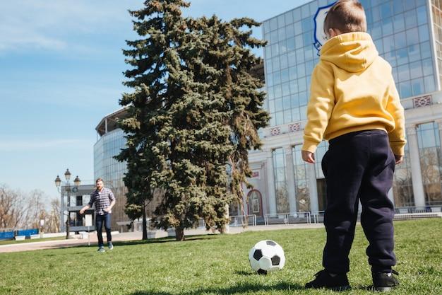 Отец, играя в футбол с его маленький сын на открытом воздухе в парке.