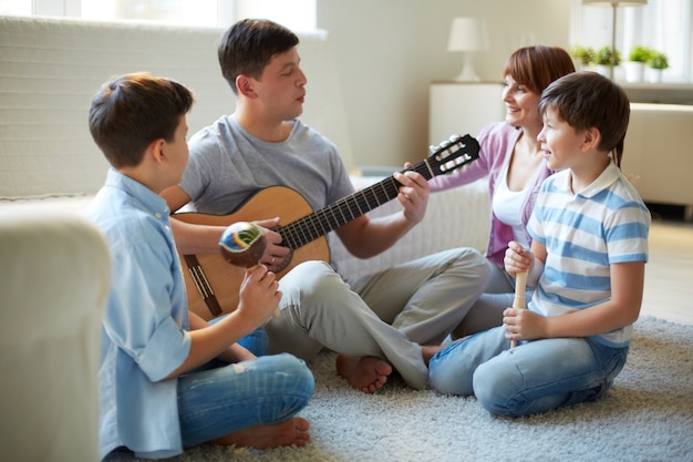 Father playing guitar at home