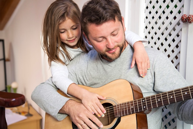 Father playing guitar with his daughter