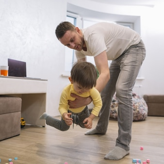 Father playing and holding his son