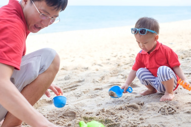 Father playing sand and beach toys with cute smiling little asian 18 months old toddler boy on sand beach