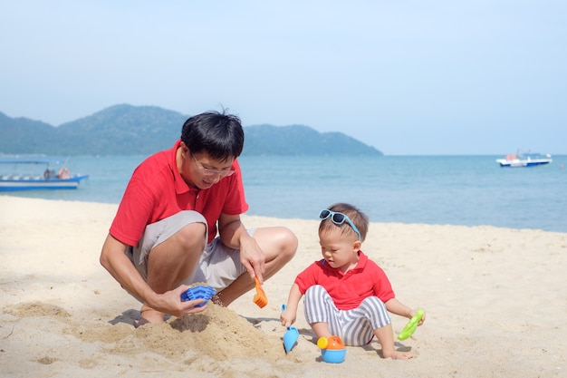 Father playing sand with cute smiling little asian toddler boy on sand beach, summer beach vacation