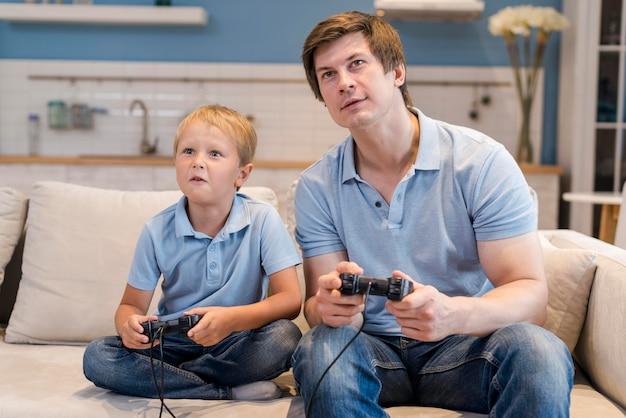 Отец играет в видеоигры вместе с сыном