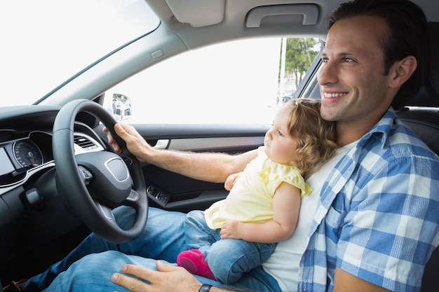 Father playing with baby in drivers seat