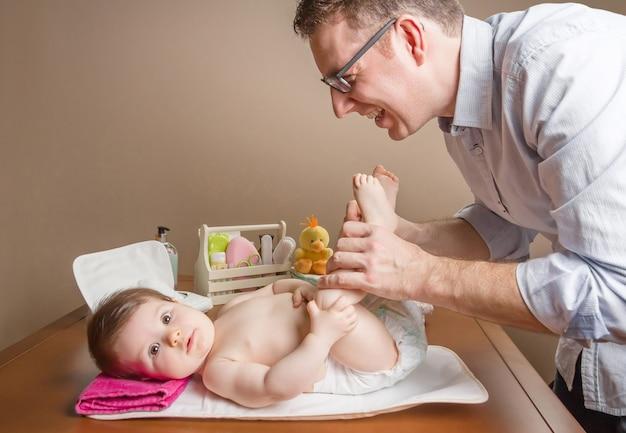 バックグラウンドで赤ちゃんのために設定されたおむつと衛生を変更した後、赤ちゃんの足で遊んでいる父