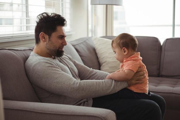 リビングルームのソファで赤ちゃんと遊ぶ父